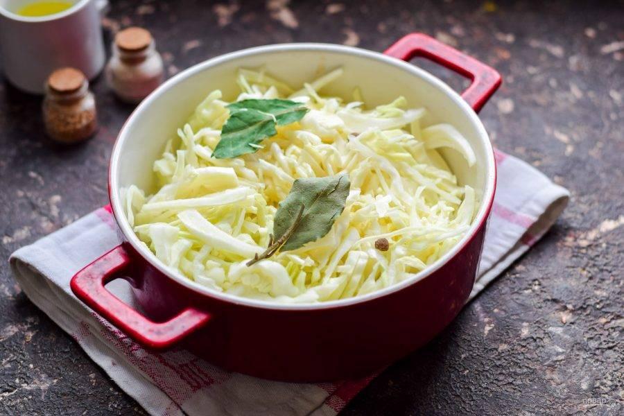 Переложите капусту в форму, добавьте масло, лавровый лист и перец горошком. Духовку прогрейте до 200 градусов.