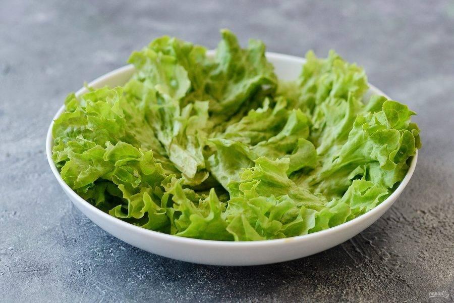 Листья салата помойте, обсушите, выложите в миску.