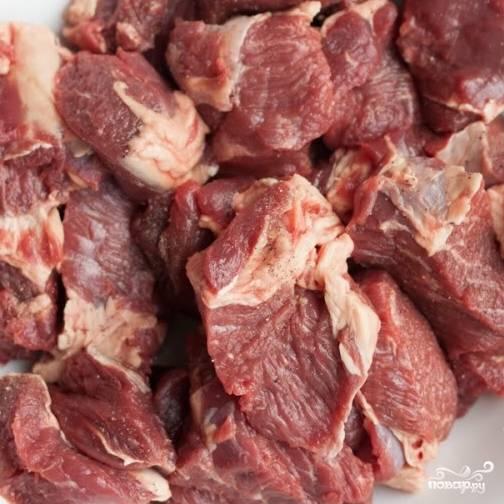 3. Промойте и нарежьте говядину небольшими кубиками. Посыпьте солью и перцем.