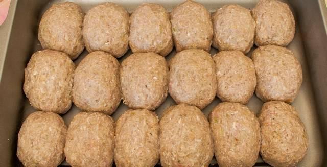 2. Смешиваем фарш, яйцо, 100 мл молока, чеснок, лук и хлеб до однородной консистенции. Лепим котлетки и выкладываем их одна к одной в форму для запекания. Форму берите с высокими бортиками, поскольку мы будем заливать наши котлетки соусом.