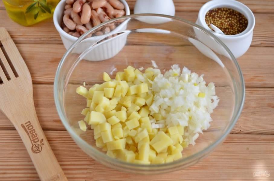 Снимите кожуру с картофеля, порежьте его кубиками. Добавьте маринованный лук.