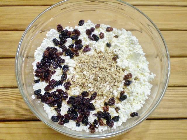 5. В творог добавляем изюм, орехи и сахар. Перемешиваем вилочкой.