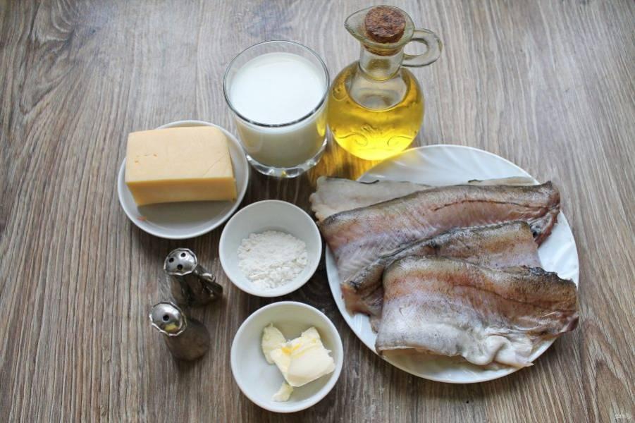 Подготовьте все необходимые ингредиенты для приготовления минтая, запеченного в сырном соусе. Сыр натрите на средней терке и разделите на две равные части.