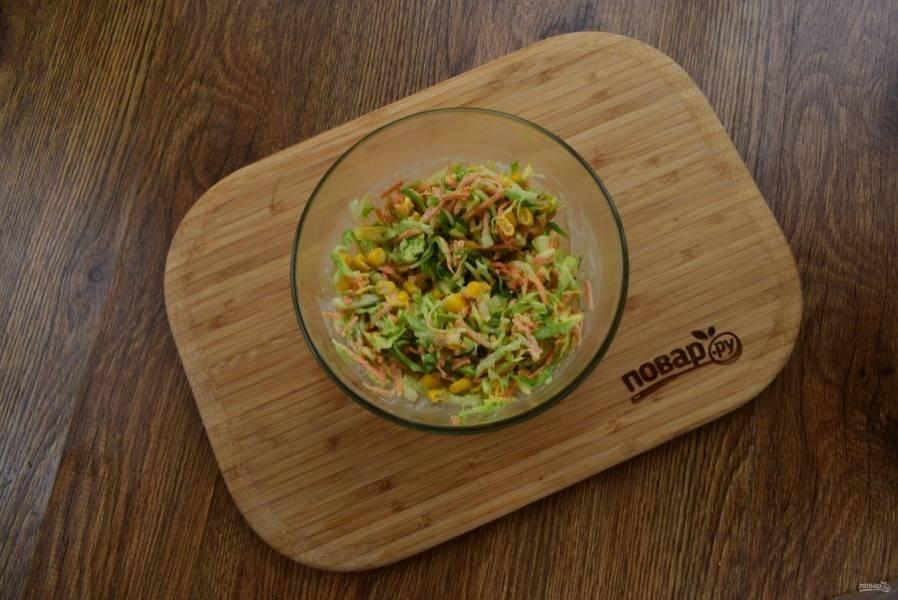Добавьте консервированную кукурузу. Перемешайте все в миске.  Чеснок измельчите и соедините с майонезом. Заправьте салат.