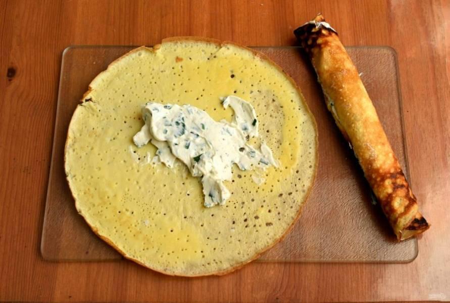 Смешайте творожный сыр с рубленной зеленью и смажьте еще теплые блинчики не толстым слоем сыра. Плотно сверните блинчики в рулончики и оставьте остывать.