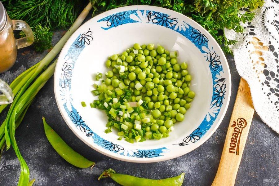 Зеленый горошек очистите, удаляя стручки. Высыпьте горошины в глубокую емкость и промойте. Промойте и измельчите зеленый лук.