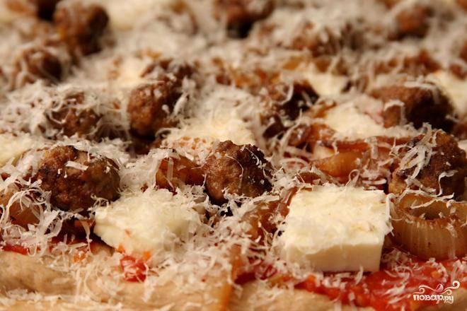 2. Между тем, поместить камень для пиццы или противень на нижнюю стойку духовки и разогреть духовку до 260 градусов. Разделить тесто пополам, сформировать из каждой шар. Дать тесту постоять от 10 до 30 минут. Обсушить помидоры и перемешать в кухонном комбайне 10-12 раз до консистенции пюре.  Выложить на сито, установленное над большой миской, и дать стечь жидкости, время от времени помешивая, в течение 10 минут. Выложить помидоры в чистую миску и размешать с ⅛ чайной ложки соли и щепоткой перца. Раскатать одну часть теста и выложить ее на камень для пиццы, выстеленный пергаментной бумагой. Выложить половину помидоров, половину Моцареллы, половину фрикаделек, половину лука и посыпать половиной тертого сыра Пармезан.