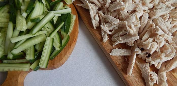 9. Куриное филе измельчите. Огурцы промойте, порежьте тонкими брусочками. Если огурцы - магазинные или с толстой шкуркой - снимите ее.