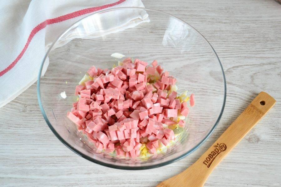 Колбасу порежьте кубиком.