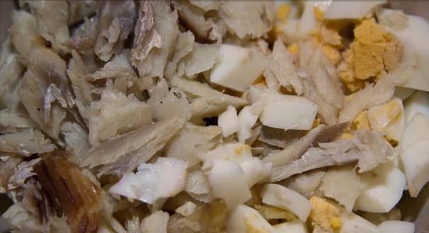 3. Для этого салат нам понадобится треска горячего копчения. Нарезаем рыбу и вареные яйца. Добавляем лук.