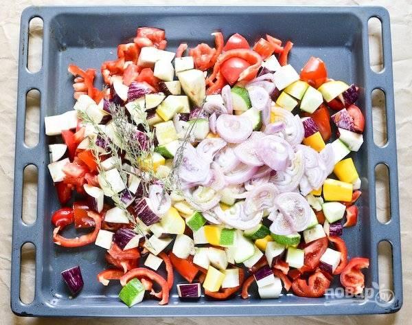 1.Нарежьте баклажаны, цуккини и томаты небольшими кубиками. Перец нарежьте ломтиками, луковицу - кольцами, чеснок измельчите. Выложите овощи на противень.
