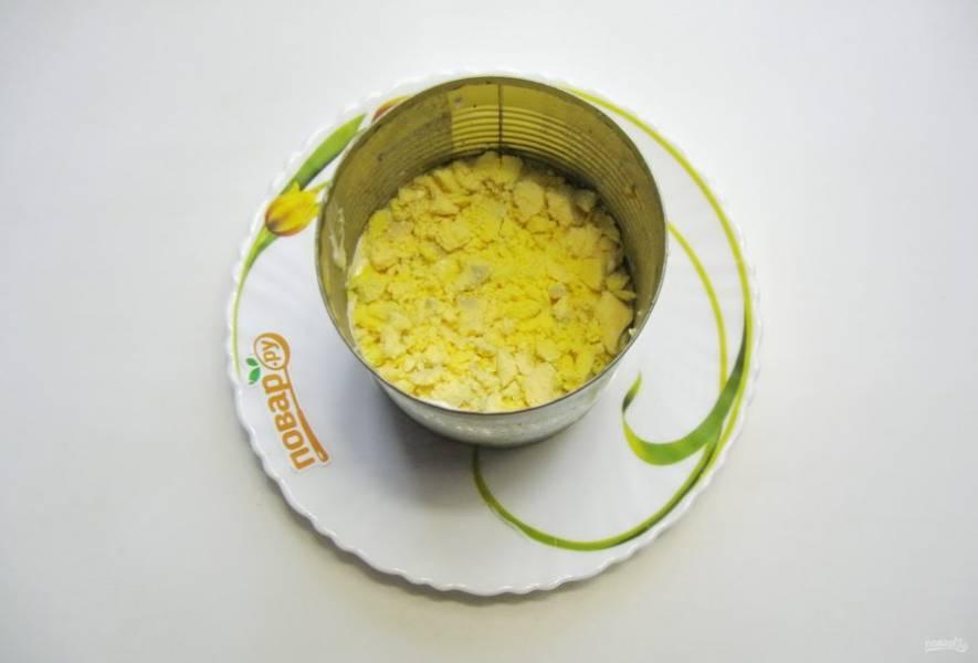Желтки разомните вилкой и выложите на слой белков.