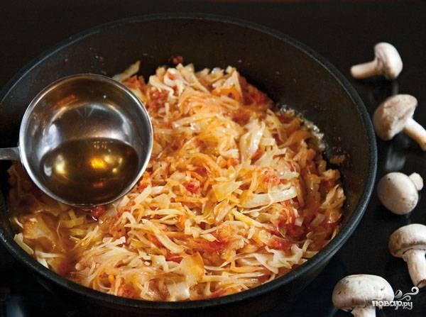 Теперь введите сырую капусту. Ее должно быть обязательно больше, как минимум в два раза. С капустой положите лавровый лист и перец горошком. Накройте крышкой, томите пятнадцать минут, пока капуста не пустит свой сок.