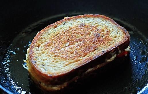 Разогреваем сковородку (на среднем огне), растапливаем сливочное масло и обжариваем бутерброд с двух сторон по 2-3 минуты. За это время должен успеть расплавиться сыр и появиться румяная корочка.