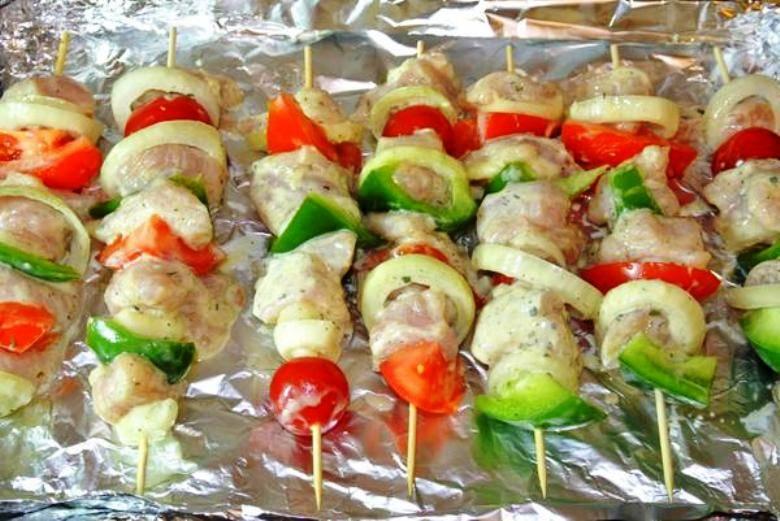 Насадите на деревянные шпажки мясо, чередуя его с овощами. Застелите противень фольгой, разложите на ней шпажки, отправьте в разогретую до 200 градусов духовку на 35-40 минут. При этом периодически переворачивайте шпажки, чтобы прожарка была равномерной. На стол подайте в горячем виде с гарниром на ваш вкус.