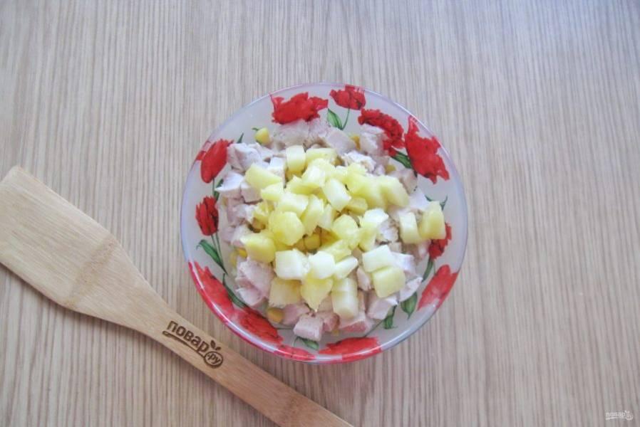 Ананас нарежьте кубиками, выложите в салатник.
