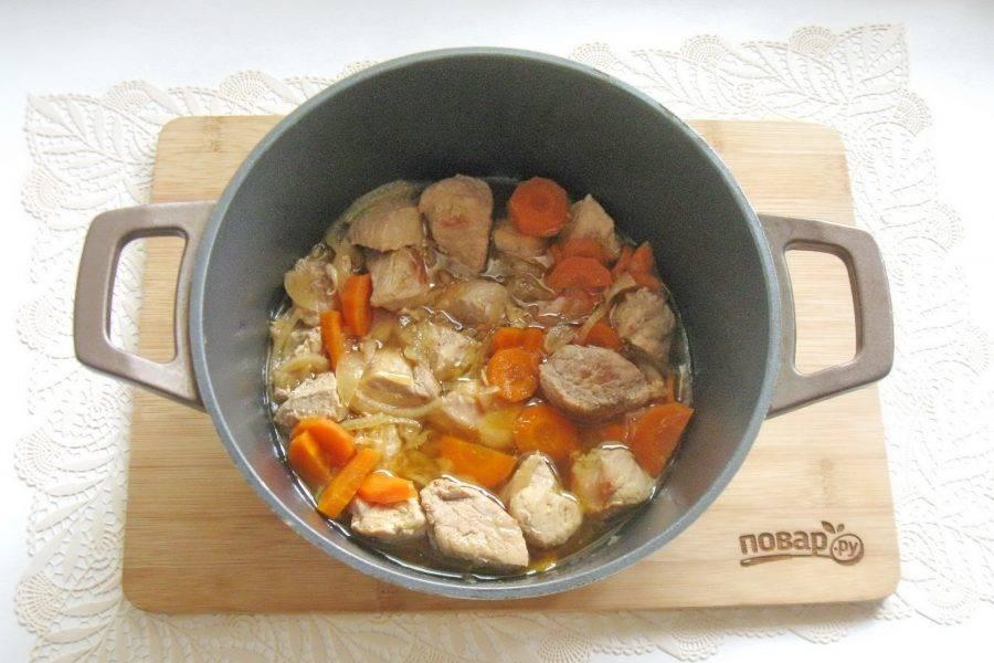 Накройте казан крышкой и тушите свинину с морковью и луком до готовности на небольшом огне.
