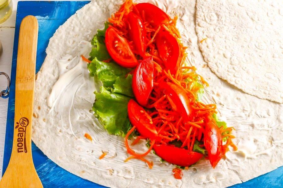 Промойте помидоры и нарежьте их на части, срежьте зеленые сердцевинки. Выложите на листья салата вместе с морковью по-корейски. Закуску выбирайте по своему вкусу: острую или не острую.