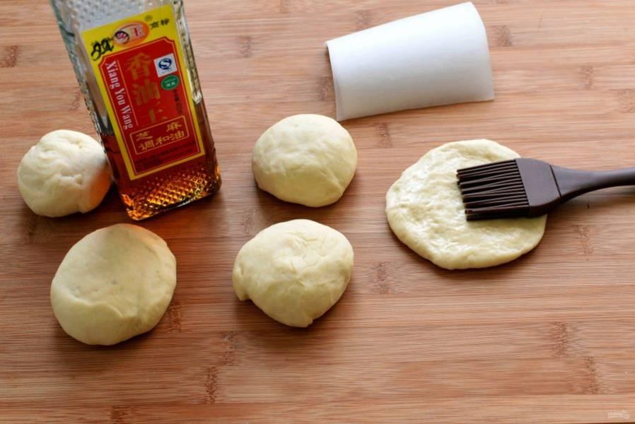 Раскатайте каждый шарик в овальную  толстую лепешечку. Смажьте кунжутным маслом и сложите вдвое. Не защипывайте, просто сверните.