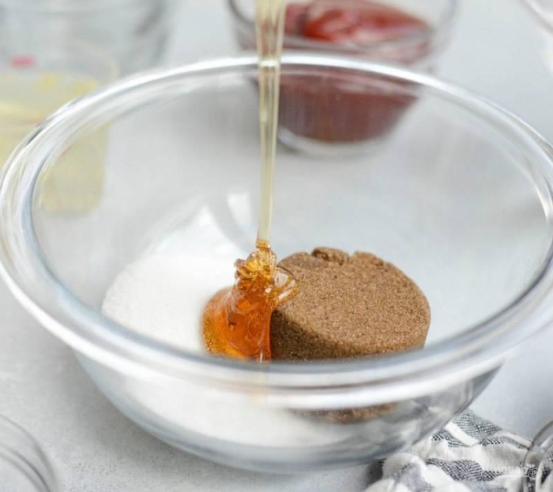 Начните с приготовления соуса. В глубокую миску добавьте весь сахар и мёд.