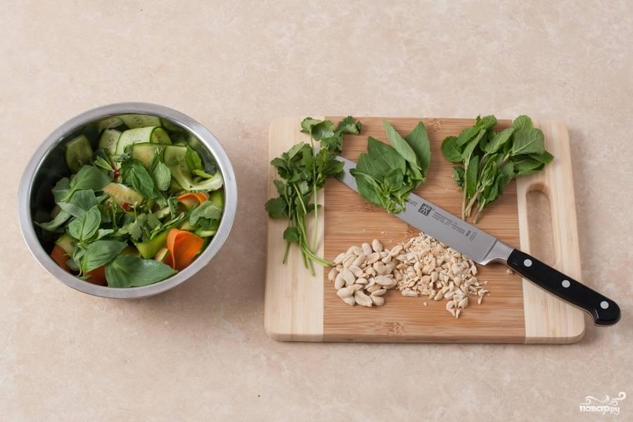 Зелень разделяем на листики, отрезая стебельки. Арахис рубим в крупную крошку. Затем в салат добавляем базилик и мяту. Все перемешиваем.