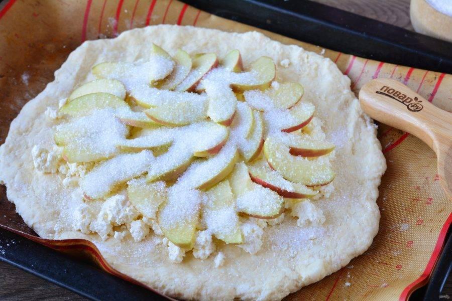 Сверху выложите нарезанные дольками яблоки. Щедро присыпьте сахаром.