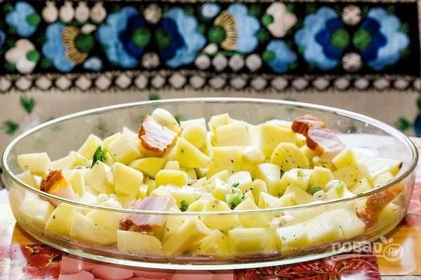 Все овощи почистите и промойте. Картофель нарежьте крупными кубиками и уложите в подготовленную форму. Добавьте нарезанный зеленый лук, чеснок, нарезанную ветчину и все перемешайте. Влейте в форму 1 стакан воды.