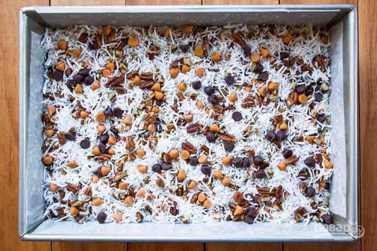 4.Посыпьте массу сначала шоколадной стружкой, потом ирисками, рублеными орехами и в заключении — кокосовой стружкой. Добавляйте только лишь в этой последовательности. Аккуратно надавите на ингредиенты ладонью, чтобы они немного погрузились в сгущенное молоко.