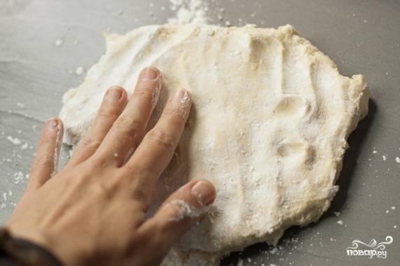 После этого времени расстелите пергамент на противне и уложите на него тесто. Сделайте лепёшки, разминая их руками.