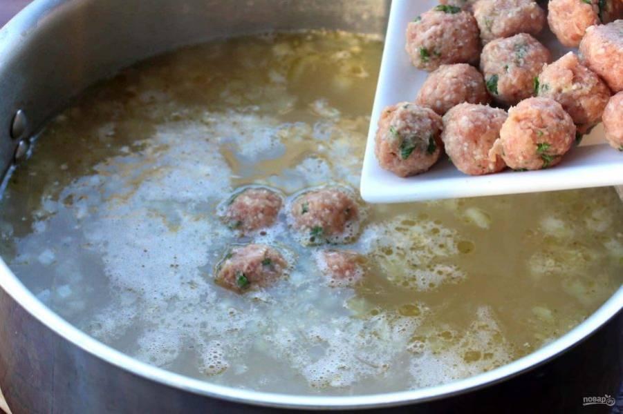 Когда лук обжарится, влейте бульон, доведите до кипения. Затем аккуратно опустите фрикадельки в суп.