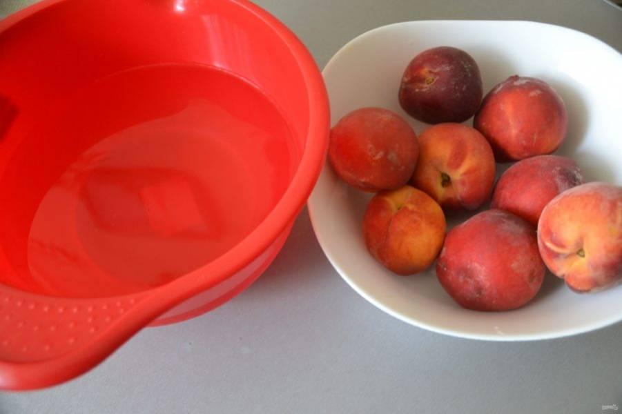 Помойте персики. Подготовьте две миски, в одну положите персики, в другую налейте холодную воду.
