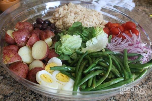 7.В миску поверх латука и бостона выложите отварные яйца, картофель, оливки, консервированный тунец, помидоры, лук и фасоль. Полейте салат оставшейся заправкой. Подавайте салат к столу.
