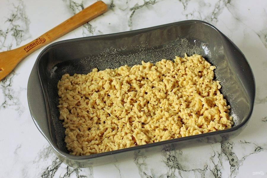 Форму для выпечки смажьте маслом. Прямо в форму натрите на крупной терке подготовленное заранее тесто и равномерно распределите его по дну.