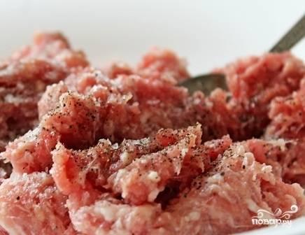 Перемешиваем фарш вместе с луком, пропущенным через мясорубку. Добавляем пол чайной ложки соли, щепотку перца и перемешиваем.