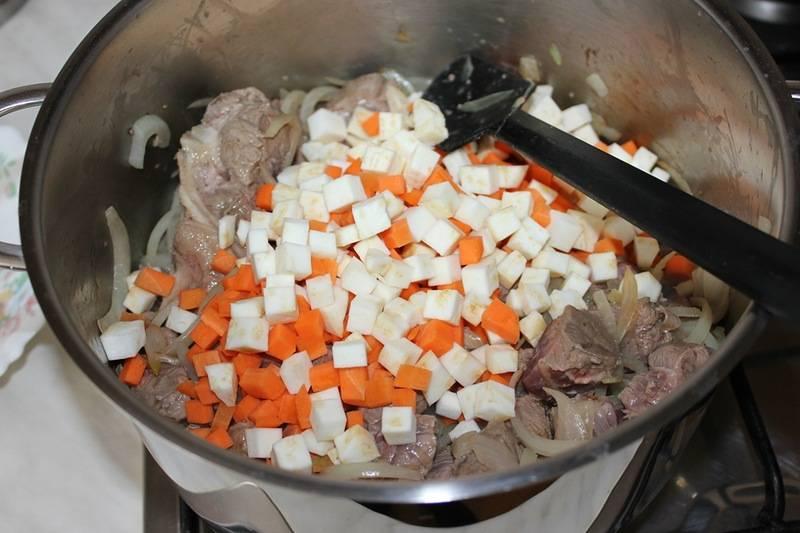 Как говядина посветлела, выкладываем в кастрюлю кубики моркови и сельдерея, жарим все до тех пор, пока овощной и мясной сок почти полностью не выпарятся. Не забываем почаще мешать ингредиенты.