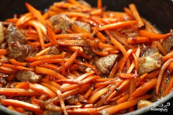 5. Минут через 8-10, когда мясо слегка обжарится, добавьте морковь. Обжарьте еще минут 5.