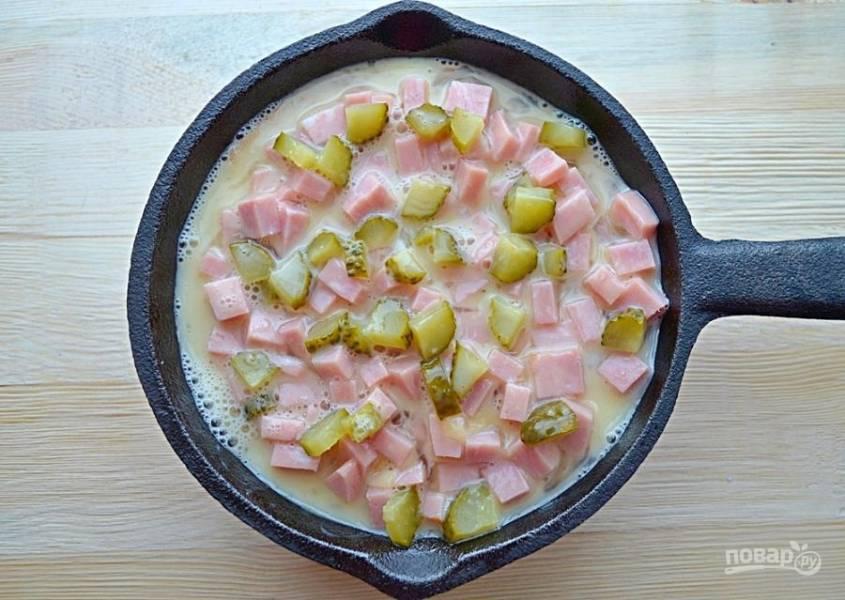 Греем духовку до 180 градусов, измельчаем огурчик, режем некрупно помидор, натираем сыр. На основу кладем огурчики, заливаем все слегка взбитыми со специями яйцами.