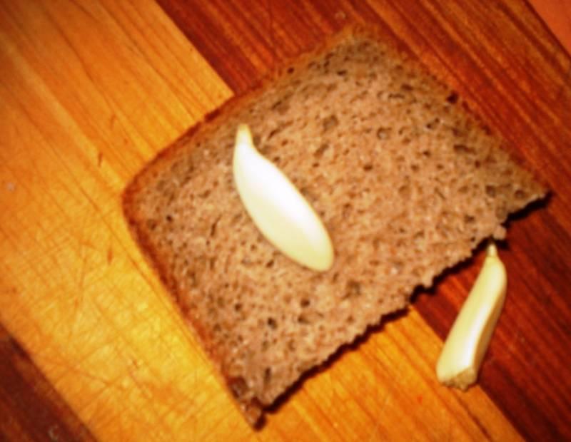 Порежьте черный хлеб и натрите каждый кусок чесноком.