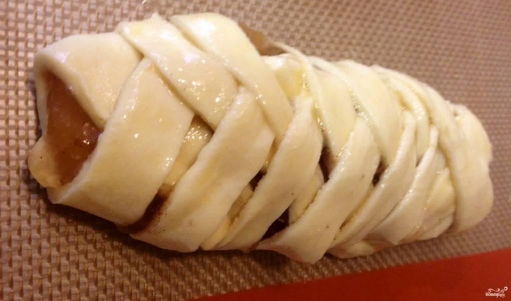 Шаг 4. на сливочный сыр выложите яблочное пюре. Заверните его в косичку. Для этого аккуратно переплетите тесто по типу плетения косы. Края скрепите как можно лучше, чтобы при запекании начинка не вытекла.