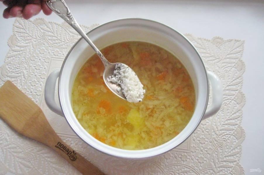Через 10 минут выложите в кастрюлю рис, который следует предварительно помыть.