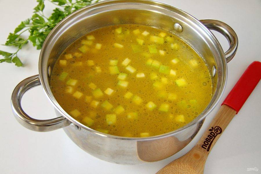 В кастрюлю налейте бульон или воду и доведите до кипения. Добавьте картофель, овощи со сковороды и соль по вкусу. Варите на среднем огне до готовности картофеля.
