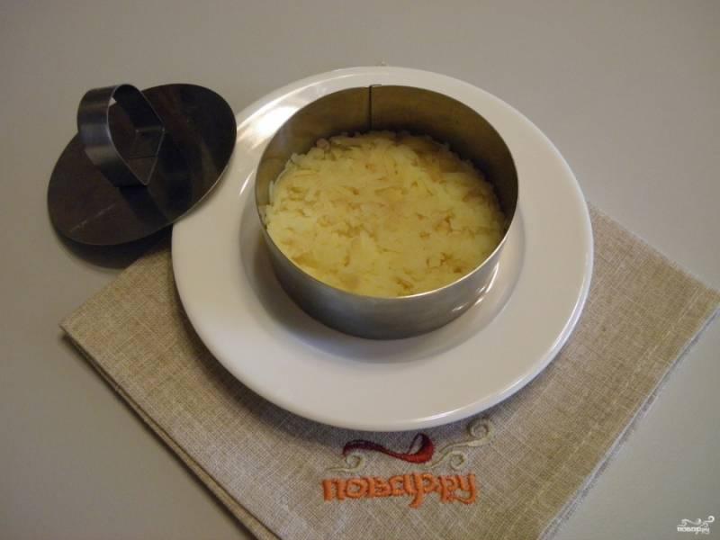 Собираем салат. На чистую тарелочку поставьте сервировочное кольцо. Первый слой салата - тертый картофель и майонезная тонкая сеточка.