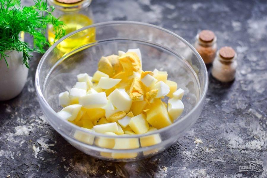 Отварите куриные яйца вкрутую, очистите и нарежьте небольшими кубиками, добавьте в салат.