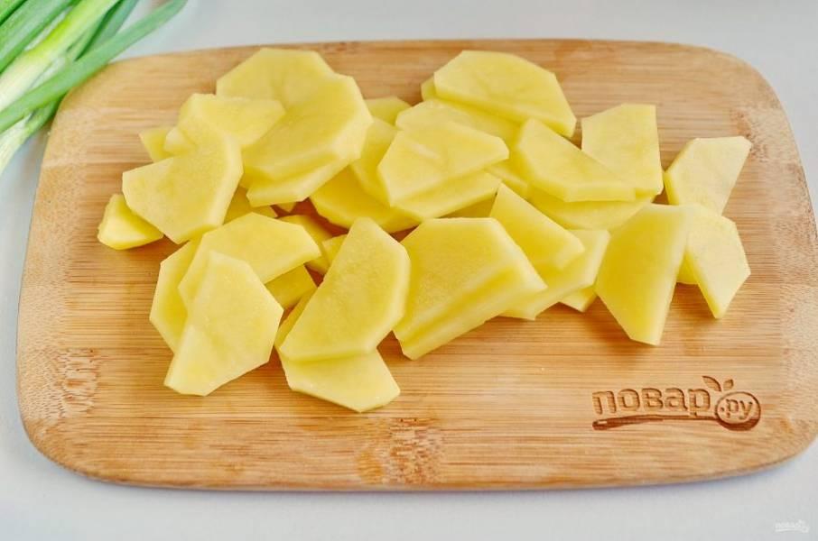 Картофель порежьте вдоль на половинки, потом каждую дольками.
