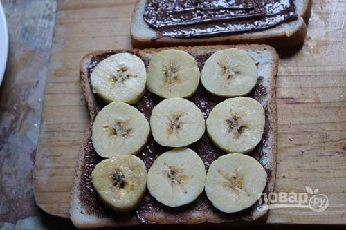 Затем на четырёх ломтиках распределите бананы.