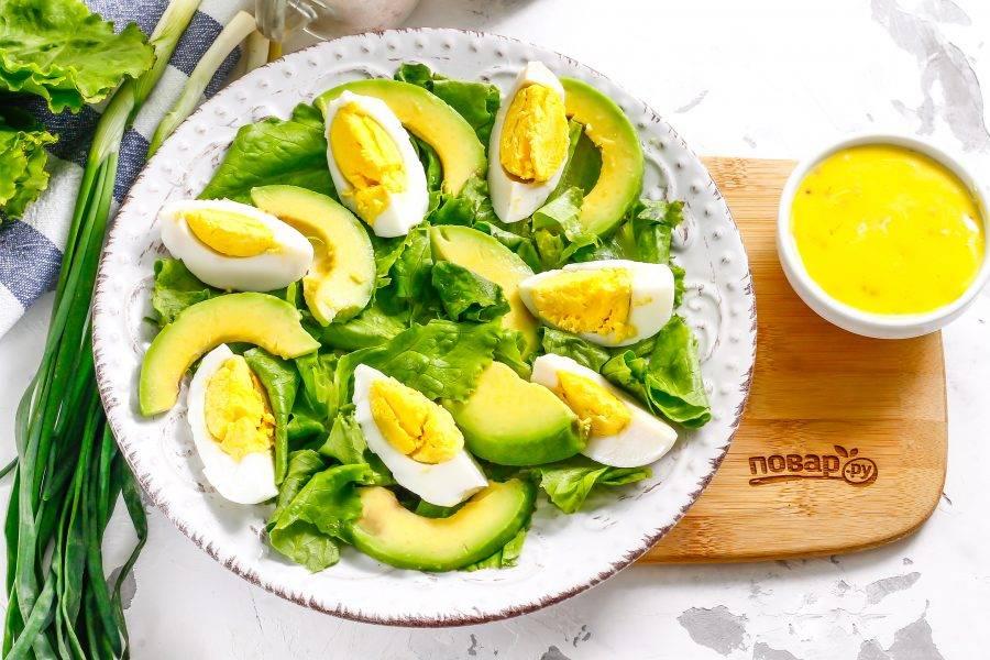 Очистите авокадо от кожуры и удалите косточку. Нарежьте мякоть слайсами и выложите на тарелку между ломтиками яичной нарезки.