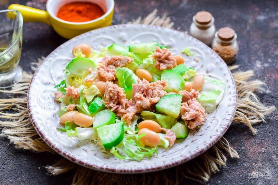Разложите в салат кусочки консервированного тунца.