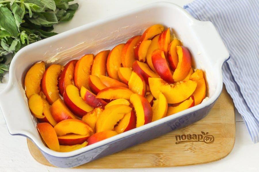 Промойте персики от ворсистого слоя на поверхности, разрежьте пополам и удалите косточки. Нарежьте ломтиками и выложите в форму.