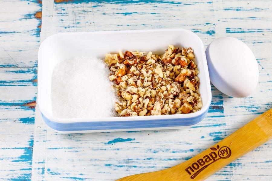 Пересыпьте ядра грецких орехов в пакет и измельчите скалкой, но не в крошку. Соедините в пиале или чашке с сахарным песком. По желанию можете добавить и ванильный сахар для аромата выпечки.