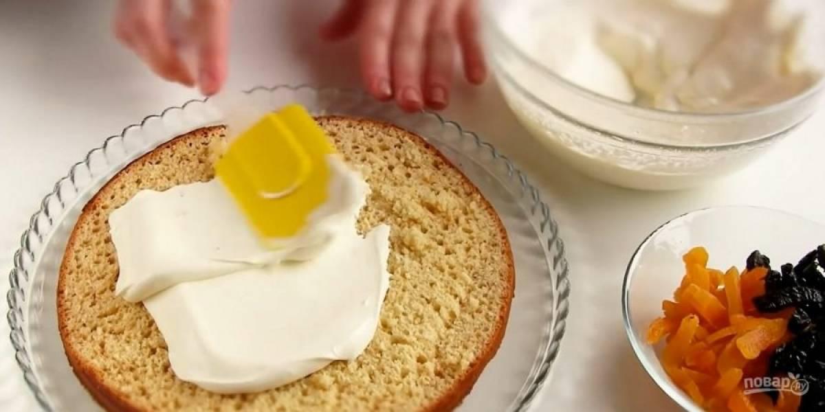 4. С остывшего коржа срежьте и измельчите верхушку, это будет крошка. Корж разрежьте на две части и смажьте кремом. Выложите на крем нарезанные курагу и чернослив.